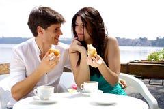 Pares no amor que come o café da manhã na frente do lago nas férias imagem de stock royalty free