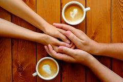 Pares no amor que guarda as mãos em um café, vista superior Fotos de Stock