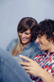 Pares no amor que olha smartphones e riso Fotos de Stock Royalty Free