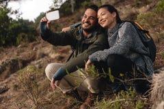 Pares no amor que senta-se na fuga de montanha e que toma o selfie fotografia de stock royalty free