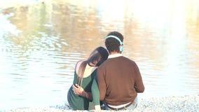 Pares no amor que senta-se pelo lago e que escuta a música com fones de ouvido video estoque