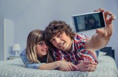 Pares no amor que toma o selfie com o smartphone na cama foto de stock