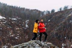 Pares no amor que viaja e que bebe o chá quente nas montanhas foto de stock royalty free