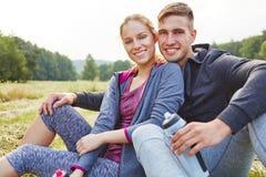 Pares no assento do amor feliz na grama Imagem de Stock