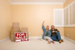 Pares no assoalho perto das caixas, sinais vendidos dos bens imobiliários Imagens de Stock