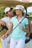 Pares no buggy do golfe imagem de stock royalty free