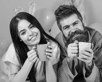 Pares no café da bebida do amor na cama Os pares relaxam na manhã com café Conceito da tradição da família Homem e mulher dentro imagem de stock royalty free