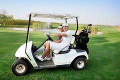 Pares no carrinho no campo de golfe imagem de stock