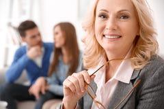 Pares no escritório de vendas dos bens imobiliários com close-up alegre de sorriso do agente fotos de stock royalty free