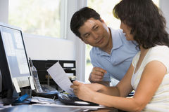 Pares no escritório home com computador e documento fotografia de stock