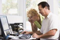 Pares no escritório home no computador que olha de sobrancelhas franzidas fotografia de stock royalty free