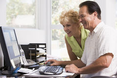 Pares no escritório home no sorriso do computador foto de stock royalty free