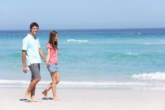 Pares no feriado que anda ao longo da praia de Sandy Fotos de Stock