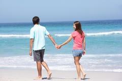 Pares no feriado que anda ao longo da praia de Sandy Fotos de Stock Royalty Free