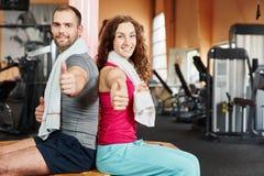 Pares no fitness center que mantém os polegares Fotografia de Stock Royalty Free