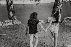 Pares no seu passeio das partes traseiras feliz para um lago na natureza Fotografia de Stock Royalty Free
