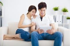 Pares no sofá com tablet pc imagens de stock royalty free