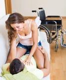 Pares no sofá perto da cadeira de rodas Imagens de Stock Royalty Free