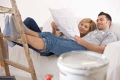 Pares no sofá que olha em casa o plano da renovação fotografia de stock royalty free