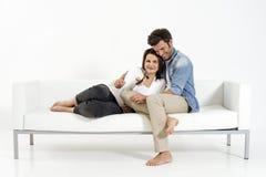 Pares no sofá que presta atenção à tevê Fotos de Stock Royalty Free