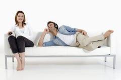 Pares no sofá que presta atenção à tevê Foto de Stock