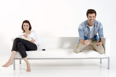 Pares no sofá que presta atenção à tevê Fotos de Stock