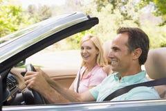 Pares no sorriso convertível do carro foto de stock
