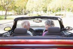 Pares no sorriso convertível do carro fotografia de stock royalty free
