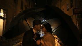 Pares noir-denominados bonitos sob a chuva que beija na rua da noite na chuva Emparelhe guardar guarda-chuvas, homem novo que jog filme
