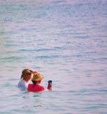Pares nos chapéus e nas camisas com coctails no oceano Foto de Stock Royalty Free