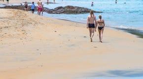 Pares nos ternos de natação que andam em uma praia fotos de stock royalty free