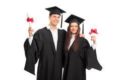 Pares nos vestidos da graduação que levantam com diplomas Foto de Stock