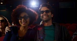 Pares nos vidros 3d que olham o filme no teatro 4k vídeos de arquivo
