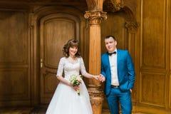 Pares, novia feliz y novio llevando a cabo las manos en el interior de madera de lujo fotos de archivo libres de regalías