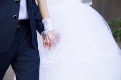 Pares, novia hermosa y novio de la boda llevando a cabo las manos Imagen de archivo libre de regalías