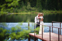 Pares, novia hermosa y novio jovenes de la boda presentando en fondo del lago El novio y la novia en el embarcadero imagen de archivo