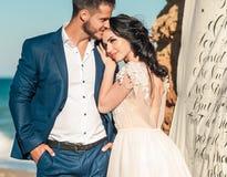 Pares, novio y novia de la boda en vestido de boda cerca del mar en la playa Foto de archivo libre de regalías