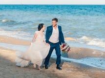 Pares, novio y novia de la boda en vestido de boda cerca del mar en la playa Fotografía de archivo libre de regalías