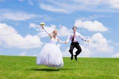 Pares novo-casados de salto Fotografia de Stock Royalty Free