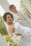 pares Novo-casados entre colunas Fotografia de Stock Royalty Free