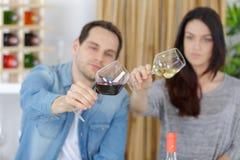 Pares novos à moda de sorriso que guardam copos de vinho na adega Imagem de Stock