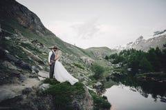 Pares novos à moda do casamento que levantam no moun bonito de Matterhorn fotografia de stock royalty free