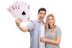 Pares novos alegres com os quatro cartões de jogo dos áss Imagem de Stock Royalty Free