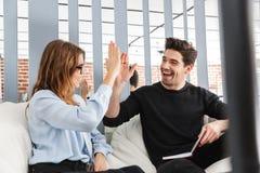 Pares novos alegres de colegas que trabalham junto fotografia de stock
