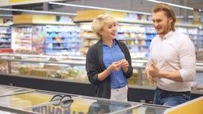 Pares novos alegres para escolher o alimento congelado no refrigerador do supermercado vídeos de arquivo