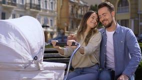 Pares novos alegres que admiram o bebê no transporte que senta-se no parque do banco, amor da família filme