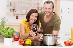 Pares novos alegres que cozinham uma refeição Fotos de Stock Royalty Free