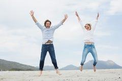 Pares novos alegres que saltam na praia Fotografia de Stock Royalty Free