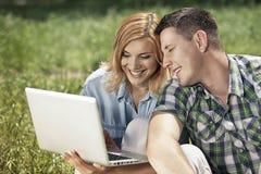 Pares novos alegres que sentam-se na grama, olhando o portátil Imagem de Stock Royalty Free