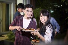 Pares novos asiáticos que apreciam um jantar e um grupo românticos de frie fotografia de stock